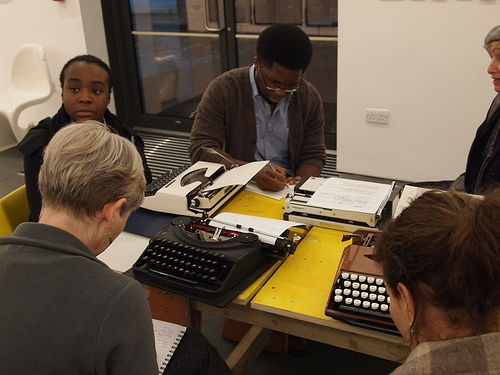 Writers working at a table with typewriters