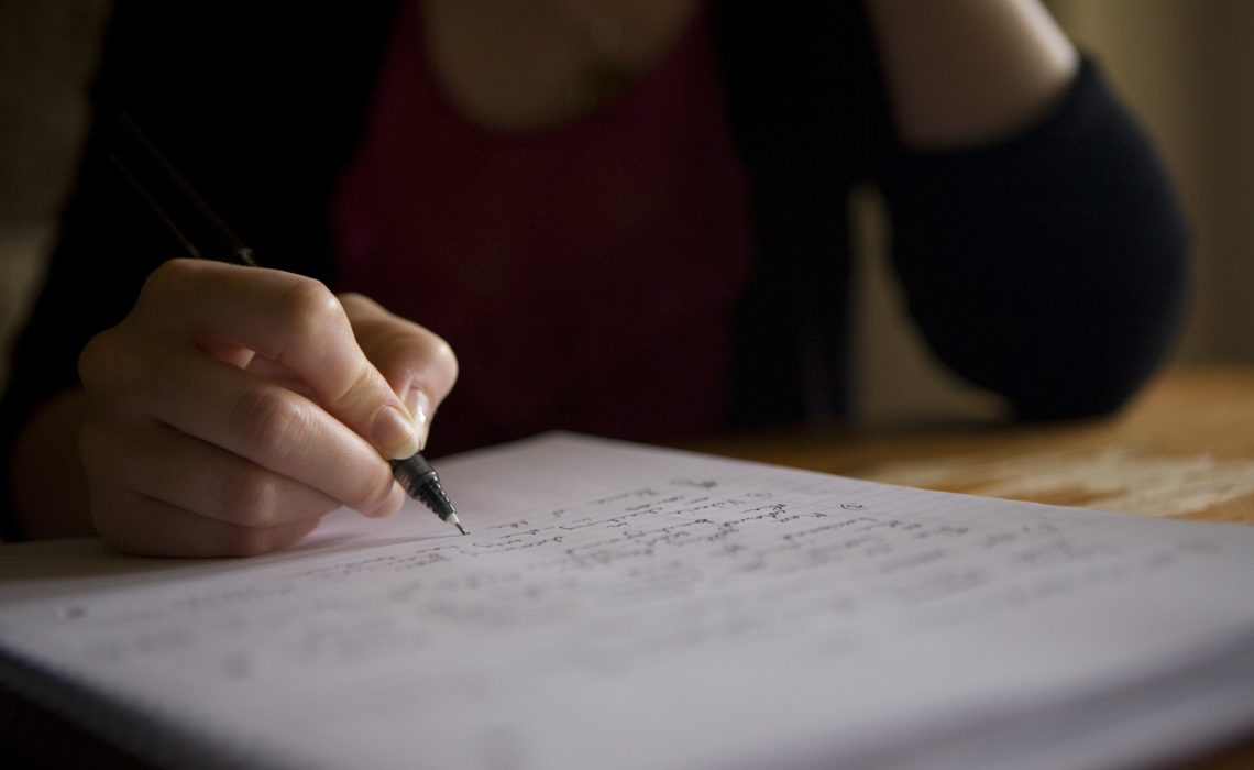 A closeup person writing in a notebook