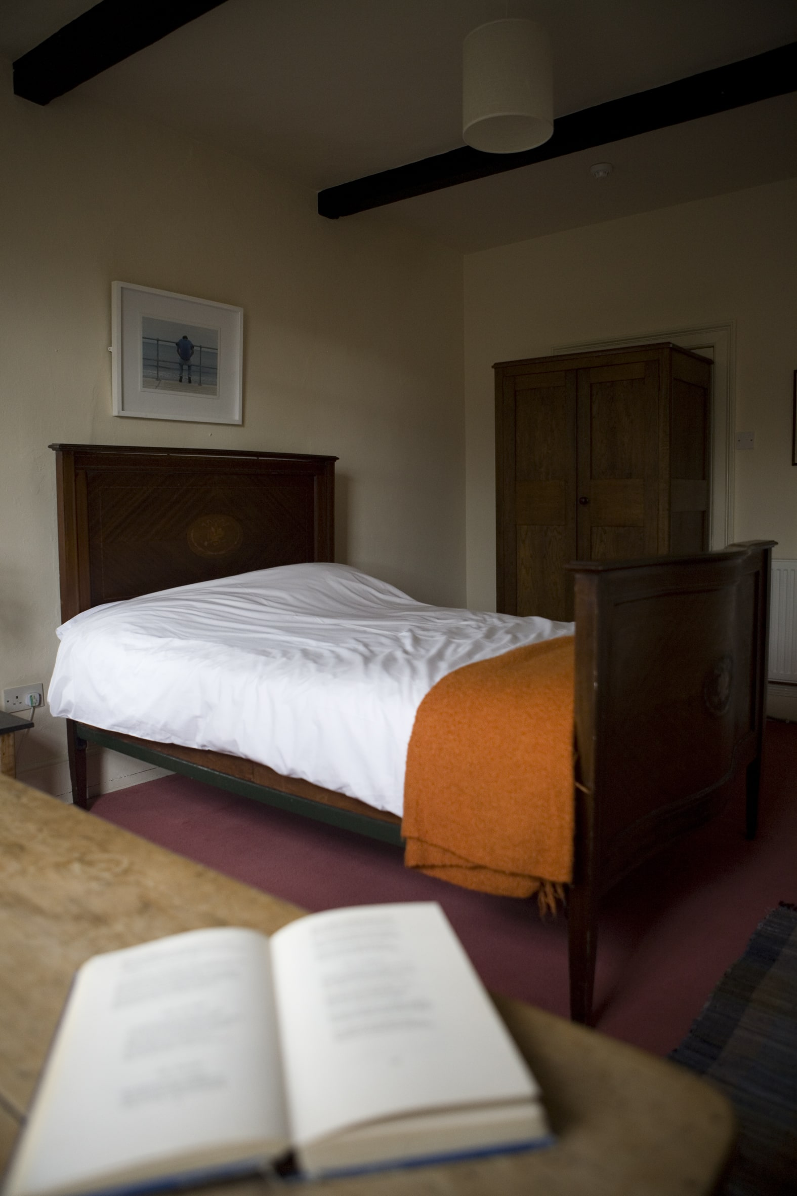 Bedroom and book on table at Lumb Bank