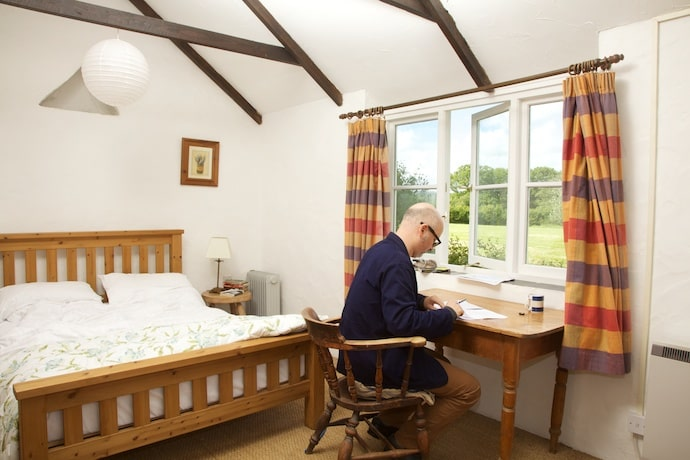 Writer at desk at Totleigh Barton bedroom