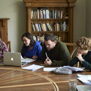 Course participants writing at the workshop table at The Hurst