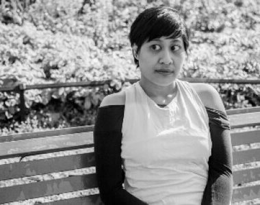 Pic description: Black and white photo of an Indonesian woman with short hair, wearing a top with off the shoulder sleeves. She is sitting on a bench with some greenery behind her